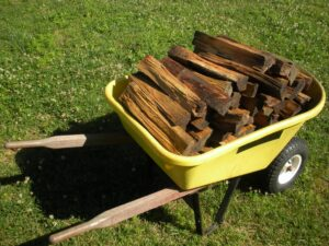 large yellow wheel barrow filled with split firewood