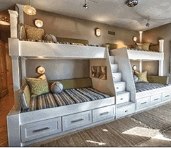 4 custom bunk beds connected with a small staircase leading up to 2 top beds located in a bedroom
