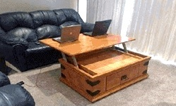 custom wooden shelf table opened and holding 2 computers in a living room with a couch
