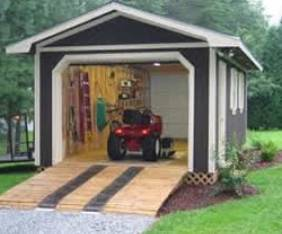gray with white trim outdoor shed with ramp leading to open door and garden tractor inside