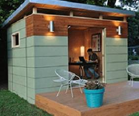 contemporary outdoor shed with open porch painted green with chairs and flower pot