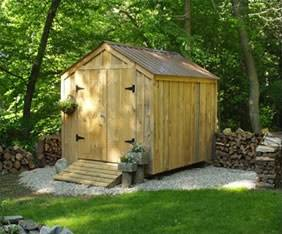 wooden shed with small ramp leading to closed door located in backyard on white stoned base