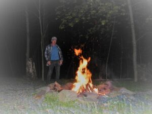man standing next to blazing fire burning in a firepit at night in the woods