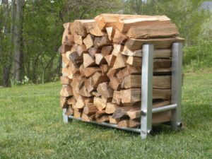 aluminum firewood holder filled with split firewood resting on green grass in backyard with trees in background