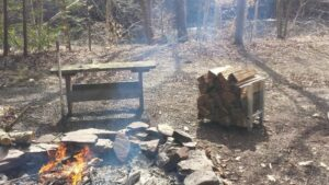 firewood holder with firewood stacked inside sitting next to burning fire in firepit with large rocks surrounding outdoors near a creek