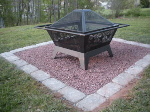 closeup of black portable firepit sitting on red stone base surrounded by white pavers in grass of backyard