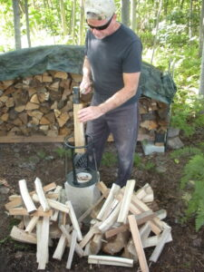 man outdoors hammering firewood in to a wood splitting tool