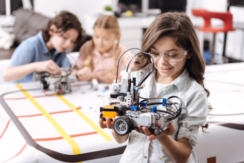 Smart generation exploring science. Sincere smiling emotional girl standing at school and holding electronic robot while her colleagues working on the project