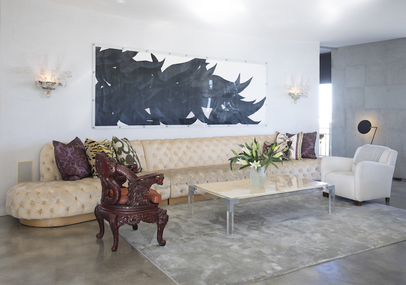 16′ custom designed tufted leather sofa in Kevin's own apartment
