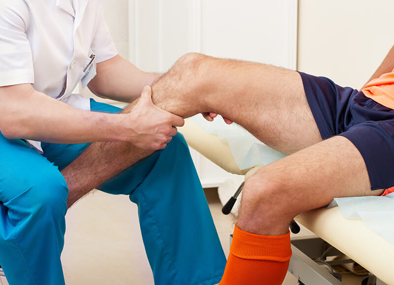 sports medicine doctor examining soccer players knee