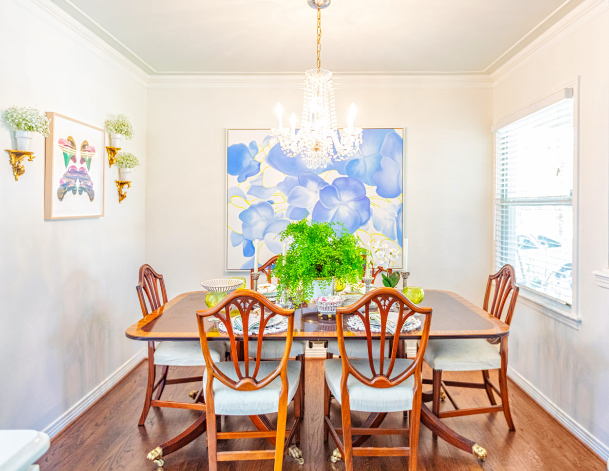 Susie Kwiatkowski's dining area with a blend of antiques and floral oil paintings.
