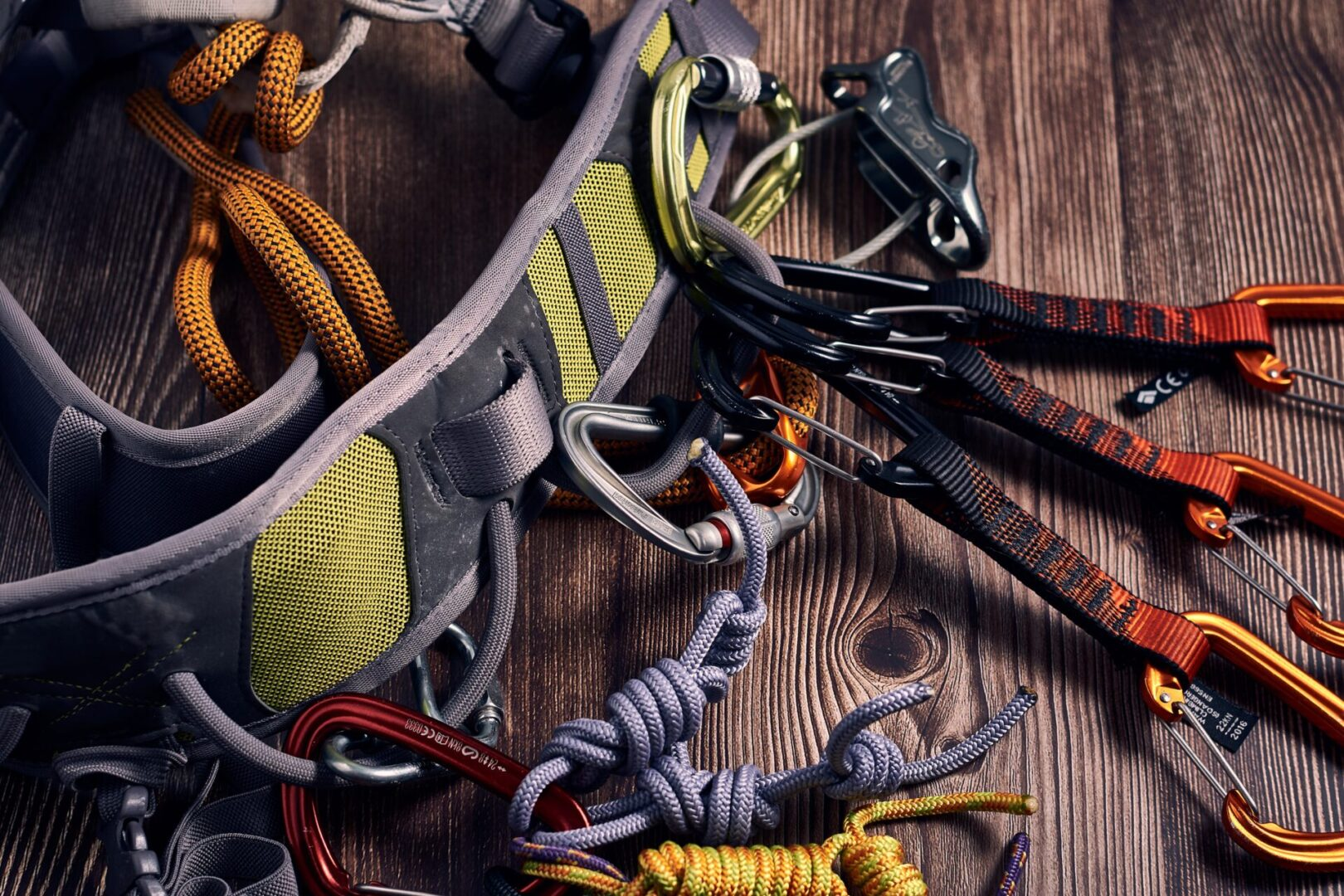 A closeup shot of many colorful climbing carabiners and knots on a wooden surface