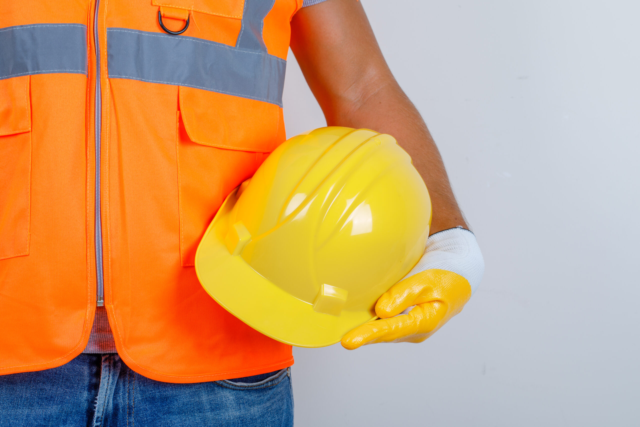 Male builder in uniform, jeans, gloves holding helmet in his hand , front view.