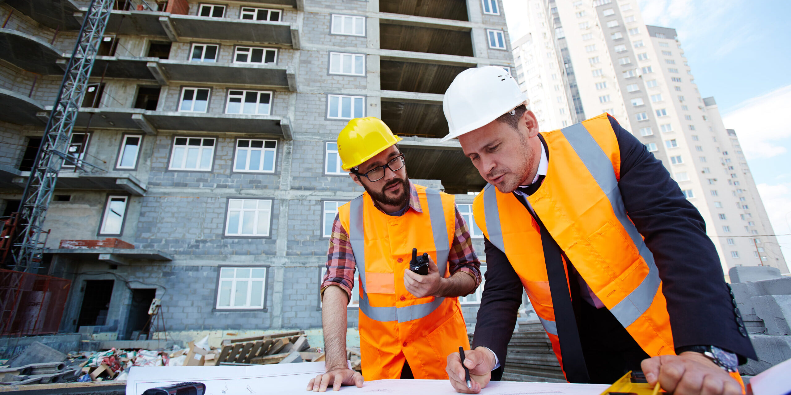 Modern engineer pointing at sketch in blueprint while explaining it to colleague