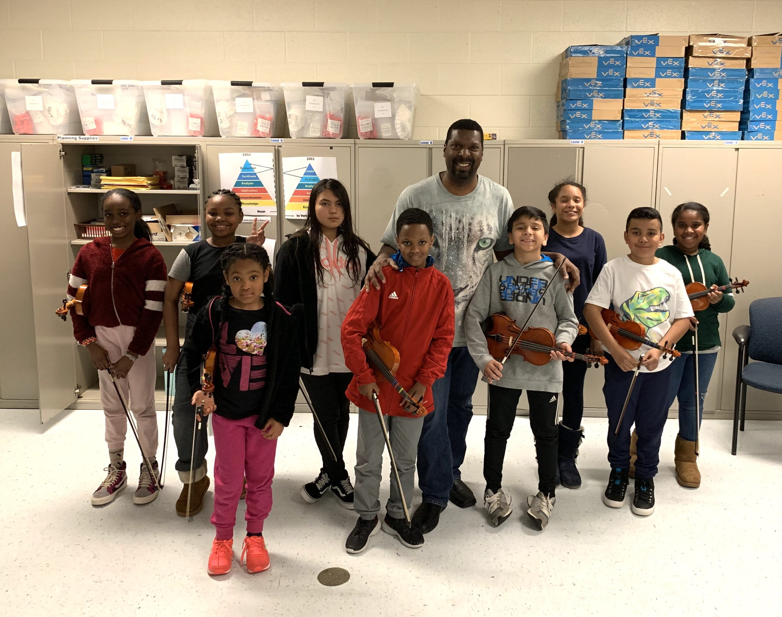 Amadi teaches a violin class for the Tapestry Music Program