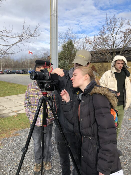 Two students using a camera to make a movie.