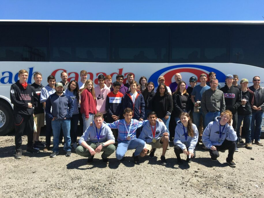 Students and staff standing and kneeling in front of a bus. Students in front row are wearing medals.