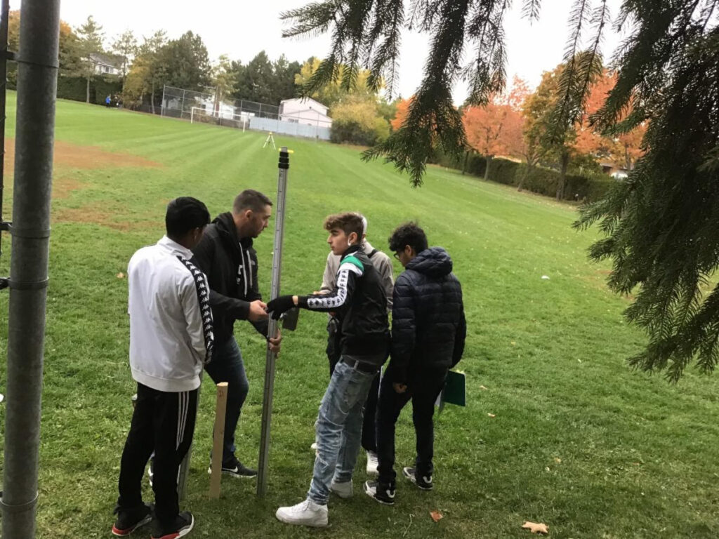 Three students and a teacher using surveying equipment in a field.