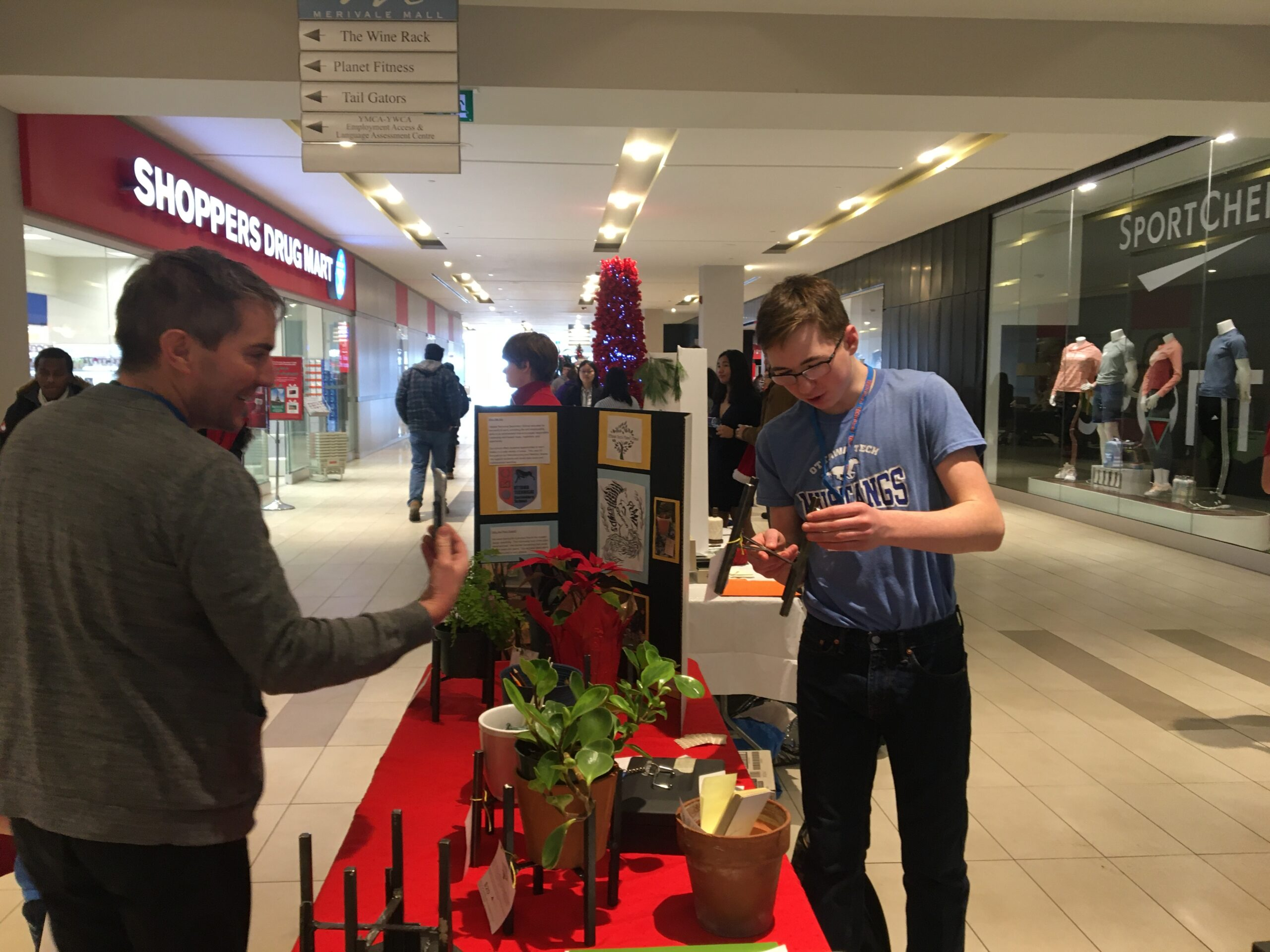 A student sells a plant stand to a customer in a mall
