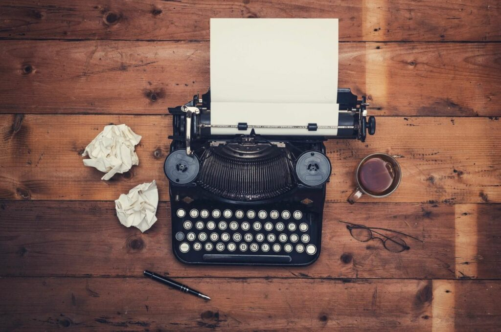 Picture of a typewriter, coffee cup and fountain pen.