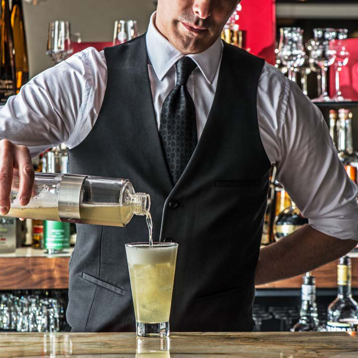 Bartender pours a mixed drink
