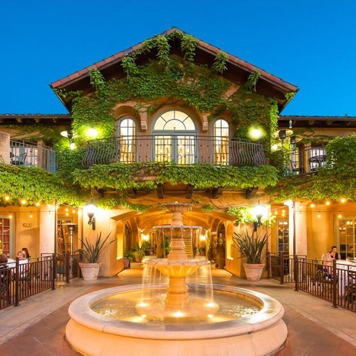 Warmly lit outdoor eating space with fountain and vine-covered walls
