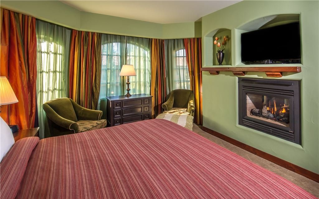 Bedroom with fireplace, armchairs, a television, and large curtained windows