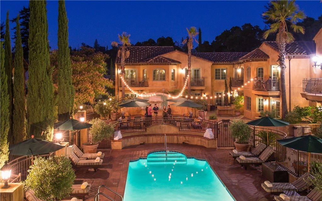 Outdoor pool and patio space lit warmly at night