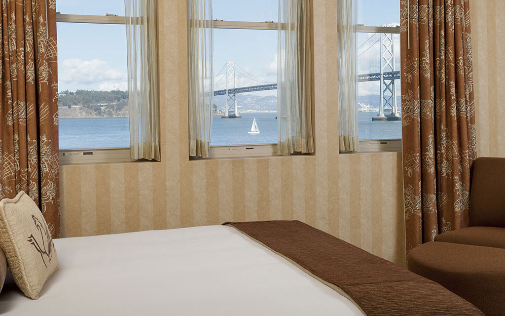Bedroom with a view of a bay and bridge