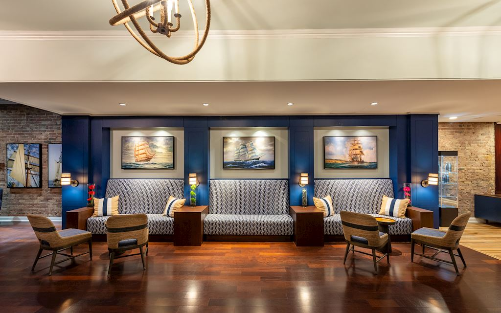 Lobby space with chairs, plush benches, and paintings of ships on the walls