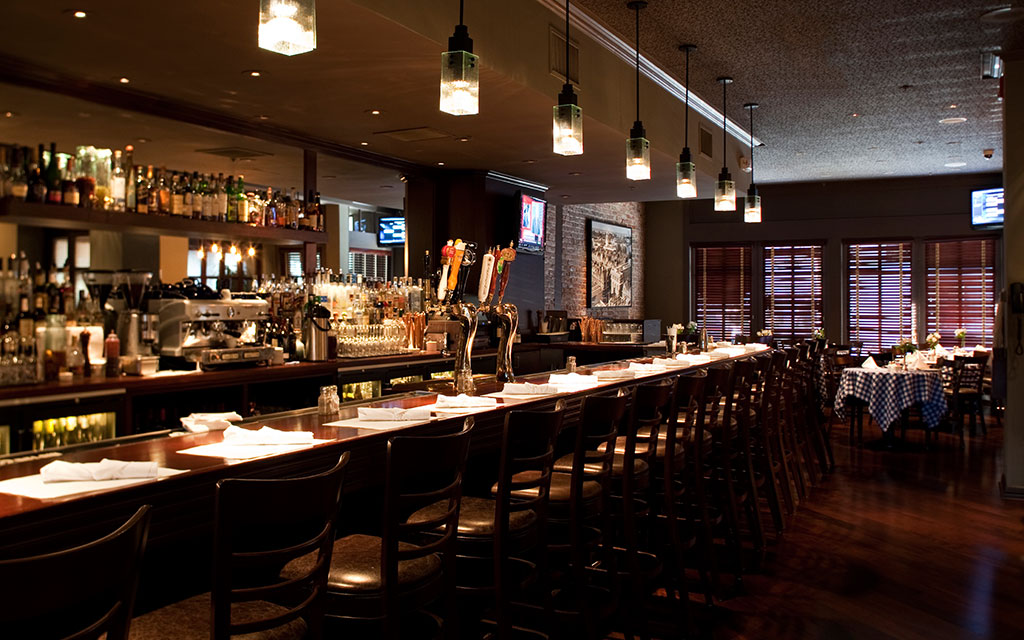 Warmly lit bar lined with barstools
