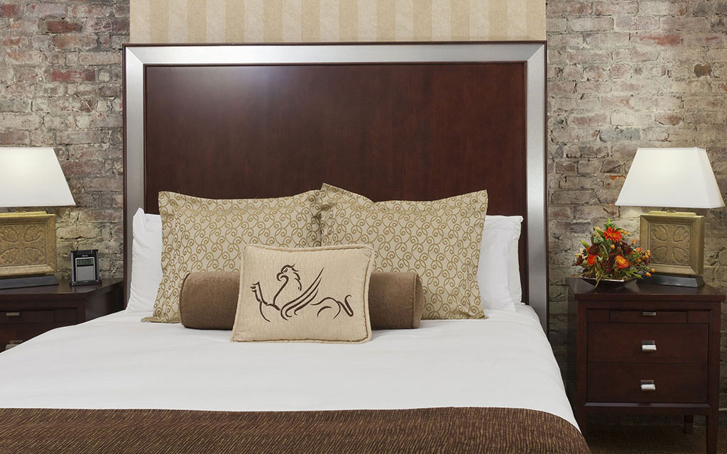 Bed topped with pillows bearing the Griffon Hotel logo