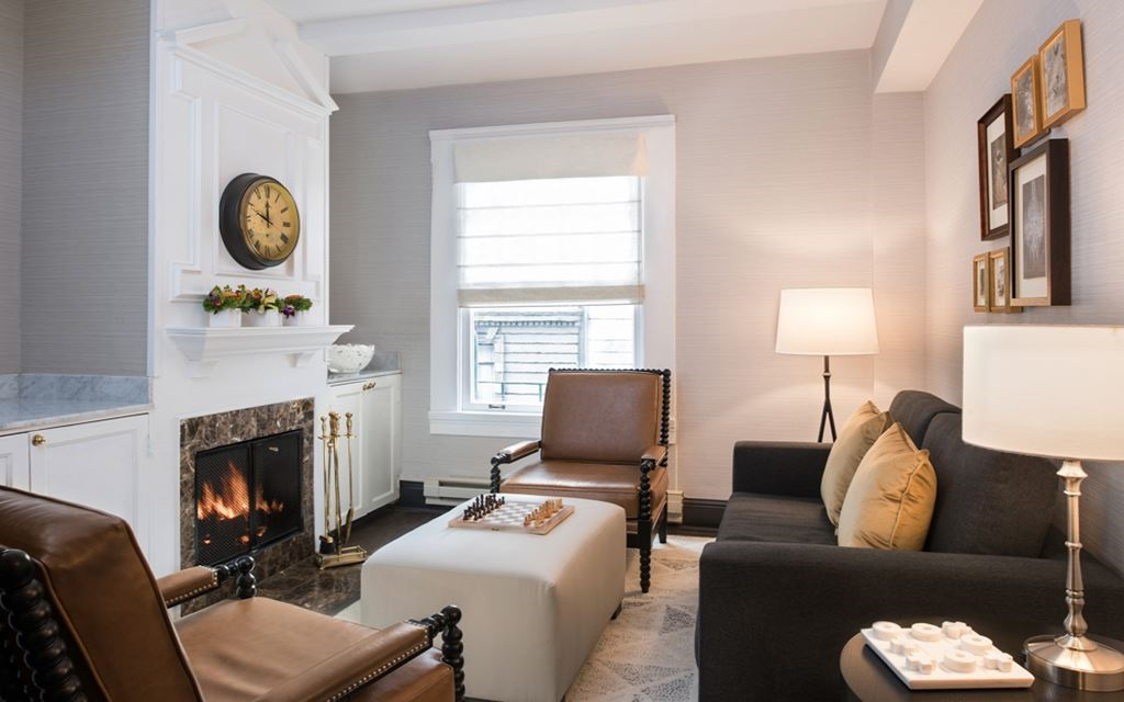 Armchairs and couches in a room with a hearth and coffee table with chess board