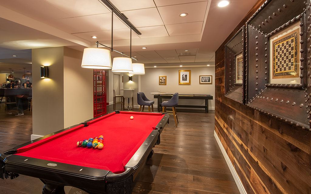 Pool table in the foreground with chairs and tables in the background