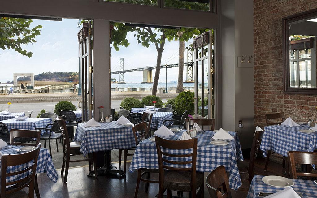 Indoor/outdoor dining space overlooking water and bridge