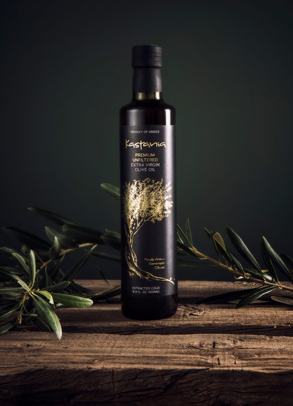 Photo of black and gold 500ml bottle of Kastania centered on wooden table on dark background