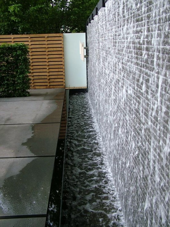 A SECLUDED HOT TUB WITH A BUBBLING WALL AND LANDSCAPING