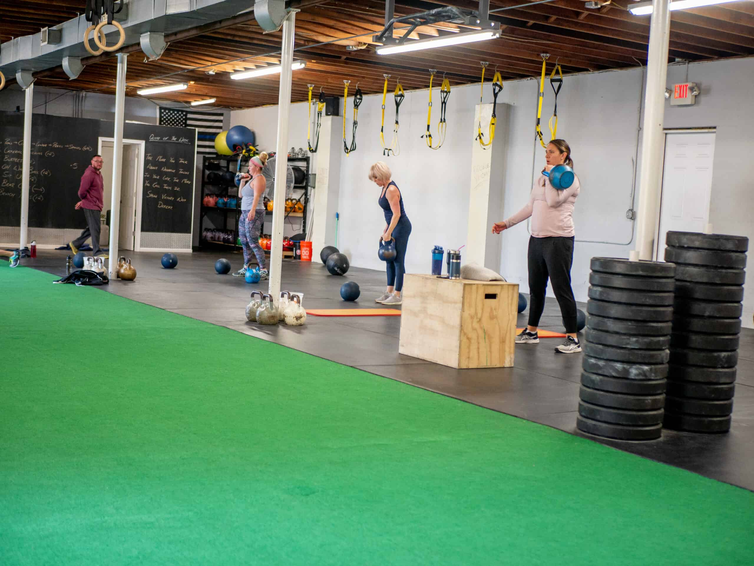 Spark Fitness team members training with kettlebells at the fitness center