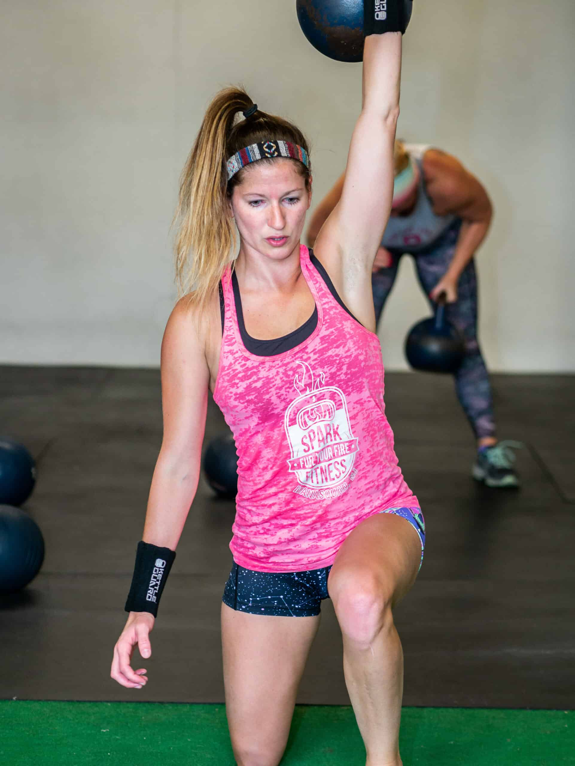 Spark Fitness team member training with a kettlebell at the fitness center