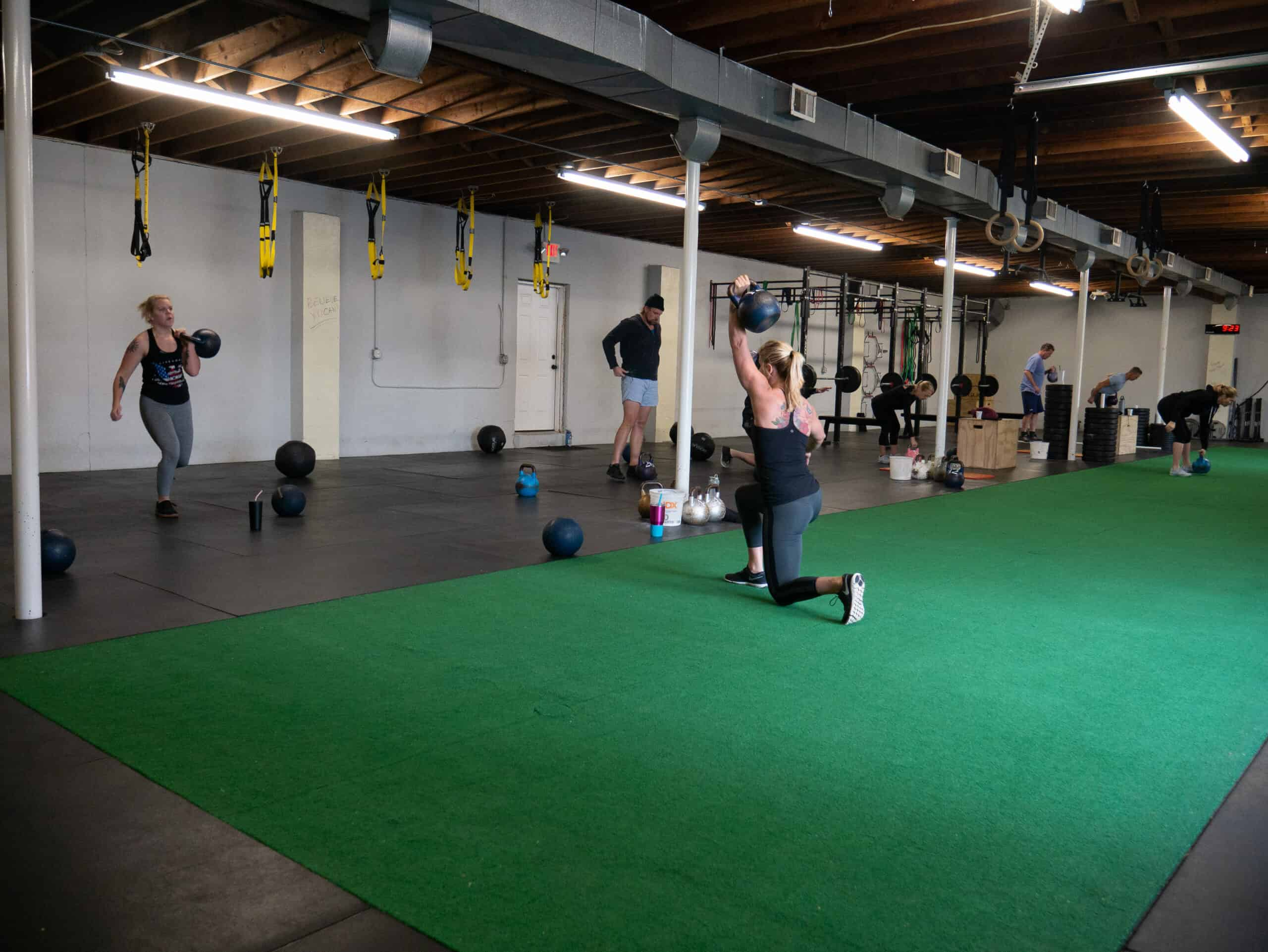 Spark Fitness team members training with a kettlebell