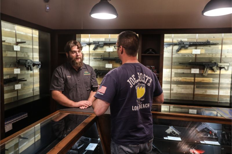 Timberline Firearms employee helping out visitor at the gun retail counter.