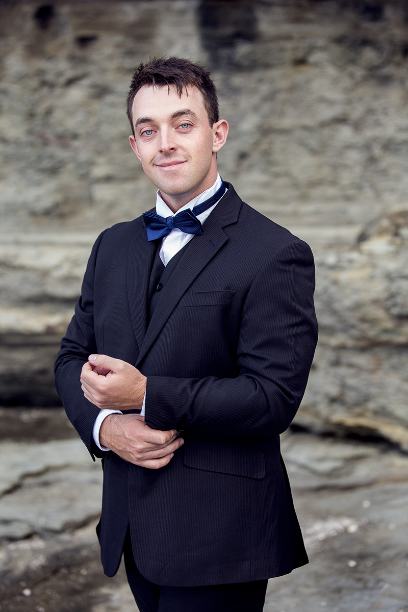 A groom in a suit and bow tie smiling at the camera on location near a beach