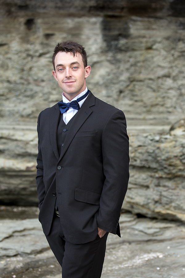 The groom in a black suit and bow tie on location at a beach during the sunset