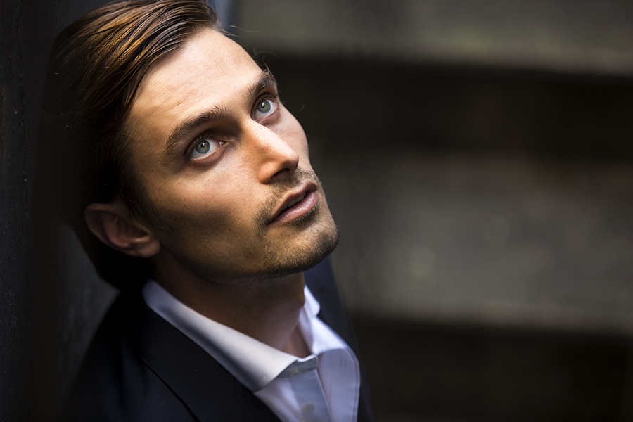A groom in a suit peering off into the distance