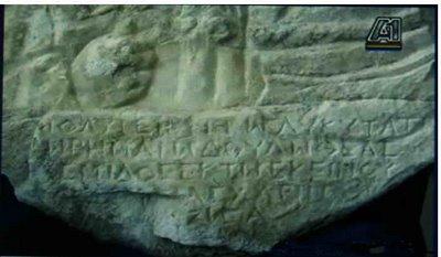 Επιγραφή από το 'εύρημα' το οποίο είναι μια βάση αγάλματος όπου υπάρχουν εγχάρακτες πέντε σειρές με γράμματα. Παρατηρήσαμε τις λέξεις που σχηματίζουν τα γράμματα αυτά. Αν και δεν είναι αρκετά ευδιάκριτα η λέξη η οποία ξεχωρίζει είναι «Η ΓΛΥΚΥΤΑΤΗ» στην πρώτη γραμμή ενώ υπάρχει μια αμφιβολία για την πριν από αυτήν λέξη «ΟΛΥΜΠΙΑΔΑ» ενώ στη δεύτερη γραμμή ξεχωρίζουν «…ΔΟΥΛΩ..».Πρόκειται, δηλαδή, για αρχαία μακεδονική επιγραφή που είναι γραμμένη στη γλώσσα των κατοίκων που ζούσαν στην περιοχή αυτή.