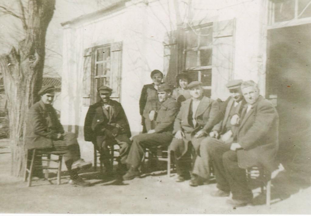 1950 - Δεκέμβριος. Μία παρέα προσφύγων κάθονται στη λιακάδα στο δυτικό μέρος του καφενείου μας με τον πατέρα μου δεξιά. Στη μέση είναι η μητέρα μου με την αδελφή μου.