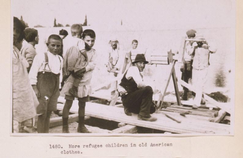 Παιδιά προσφύγων με άνδρες έξω από ένα καφενείο σε κωμόπολη της Ελλάδας το 1923. Συλλογή Frank and Frances Carpenter Collection (Library of Congress No. C262)