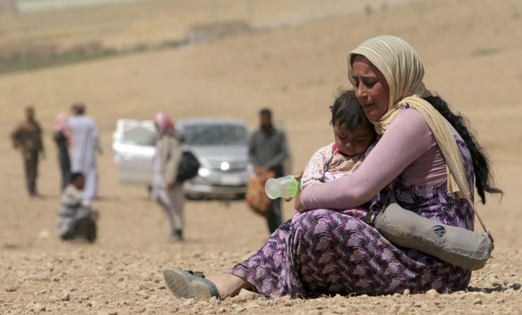 A Yazidi mother holding onto her child after ISIS terrorized their towns of Sinjar mountain - Iraq