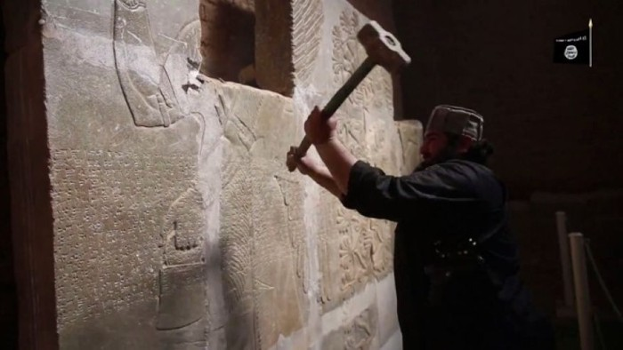 "April 11, 2015: In this image made from video posted on a militant social media account affiliated with the Islamic State group purports to show a militant taking a sledgehammer to an Assyrian relief at the site of the ancient Assyrian city of Nimrud, which dates back to the 13th century B.C., near the militant-held city of Mosul, Iraq. The destruction at Nimrud, follows other attacks on antiquity carried out by the group now holding a third of Iraq and neighboring Syria in its self-declared caliphate. The attacks have horrified archaeologists and U.N. Secretary-General Ban Ki-moon, who last month called the destruction at Nimrud ""a war crime."" (Militant video via AP)"