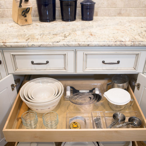 Pull out drawers in kitchen with bowls and baking utensils
